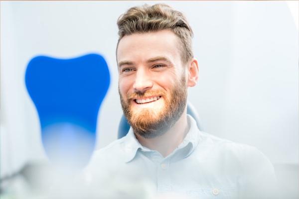 Man smiling into dental mirror